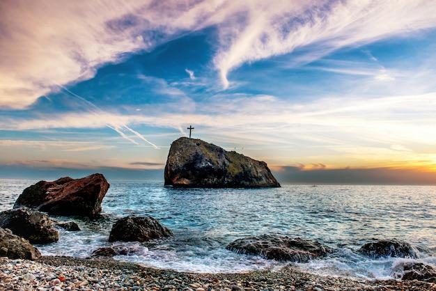 Paisagem com pôr do sol na praia do mar azul, rochas e céu dramático.