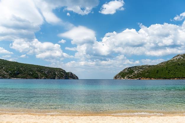 Paisagem com praia, o mar e as lindas nuvens no céu azul