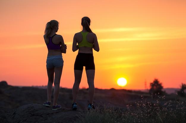 Paisagem com silhueta de jovens desportivas ao pôr do sol