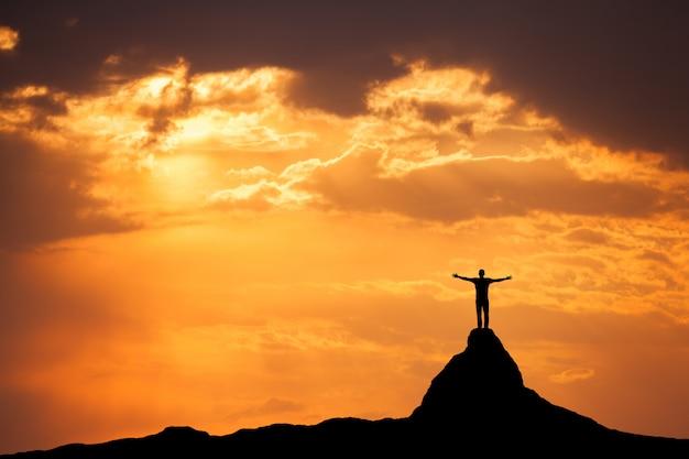 Paisagem com silhueta de um homem no pico da montanha