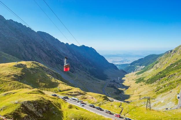 Paisagem com teleférico vermelho acima da estrada alpina transfagarasan nas montanhas dos cárpatos em dia ensolarado. .