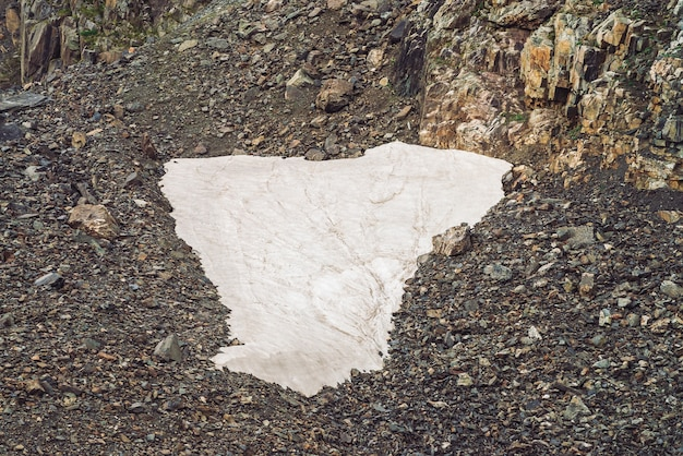 Paisagem com um pequeno campo de neve em talude em uma montanha rochosa