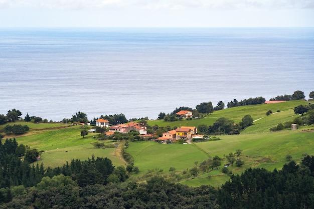 Paisagem com uma pequena aldeia, colina, floresta, mar e céu azul com nuvens