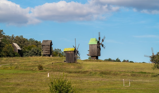 Paisagem com velhos moinhos de vento de madeira em um prado em um dia ensolarado