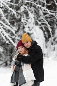 Paisagem congelada de inverno com casal abraçando