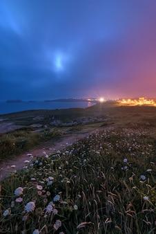 Paisagem costeira à noite com cores quentes e frias em um céu nublado