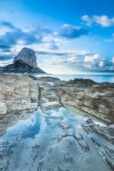 Paisagem costeira, com rochas em primeiro plano e a rocha ifach no horizonte