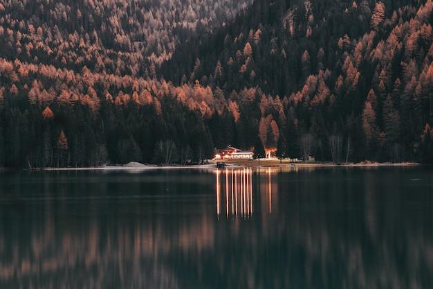 Paisagem da casa perto de madeiras e corpo de água calmo