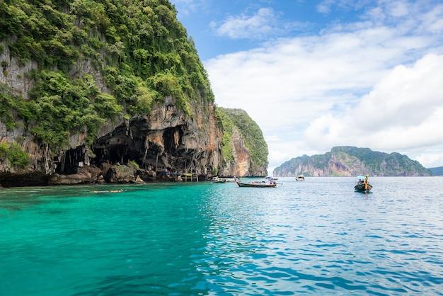 Paisagem da caverna viking com barco longtail para o viajante, baía maya, ilha phi phi, mar de andaman, krabi,