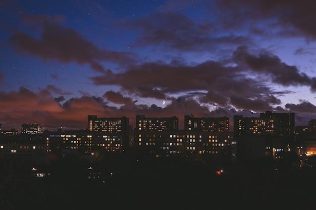 Paisagem da cidade à noite com prédios contra o céu com nuvens e a lua.
