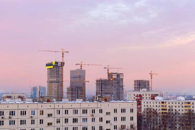 Paisagem da cidade ao amanhecer, nascer do sol com belo horizonte e edifícios em construções com guindastes