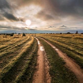 Paisagem da estrada de terra em direção às montanhas com sol no horizonte, nuvens escuras e ambiente chuvoso. riaza, segóvia.