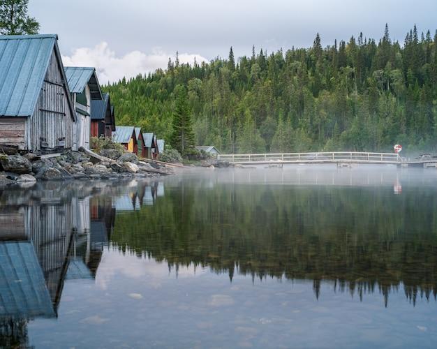 Paisagem da floresta e casas refletindo em um lago coberto de nevoeiro sob um céu nublado