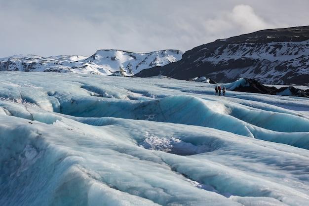 Paisagem da geleira com guia particular e casal de caminhante à distância,