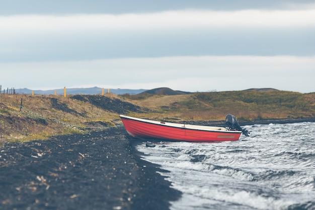 Paisagem da islândia com um barco vermelho na costa
