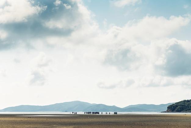 Paisagem da maré baixa com montanha verde, céu da nuvem com os povos no fundo na baía do pronuto de toong em chon buri.