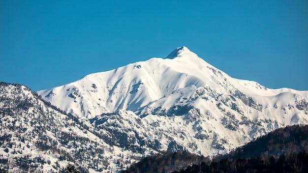 Paisagem da montanha da neve com o céu azul na montanha dos cumes de japão.