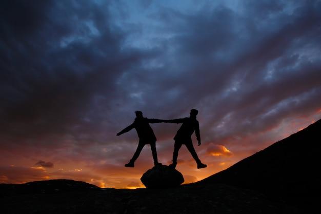 Paisagem da montanha norueguesa. pessoas de mãos dadas e de pé sobre uma grande pedra no contexto do pôr do sol