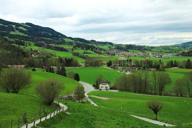 Paisagem da natureza do esclarecimento da floresta e do campo verde acima de uma vila em suíça.
