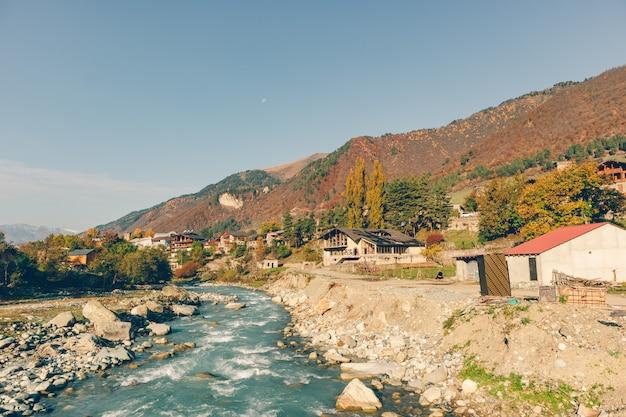 Paisagem da pequena cidade rural e o rio de mestia, geórgia.