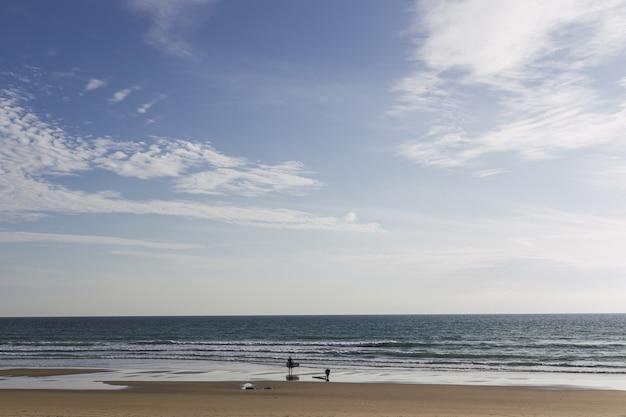 Paisagem da praia com surfistas rodeada pelo mar sob o sol durante o dia
