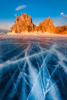 Paisagem da rocha shamanka ao pôr do sol com gelo natural no lago baikal, sibéria, rússia