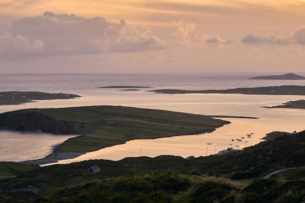 Paisagem da sky road rodeada pelo mar durante o pôr do sol em clifden, na irlanda