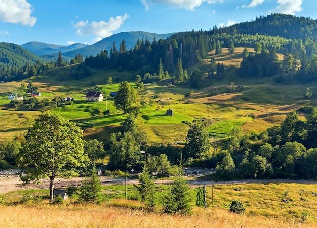 Paisagem de aldeia de montanha de verão com pastagens floridas na frente