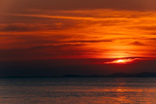 Paisagem de ardência bonita do por do sol e céu alaranjado acima dela, fundo do verão.