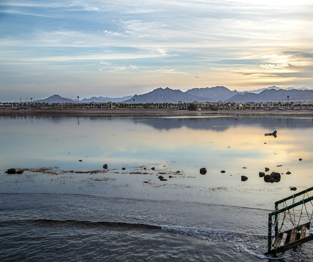Paisagem de belo espaço ao pôr do sol à beira-mar. com figuras solitárias à distância.