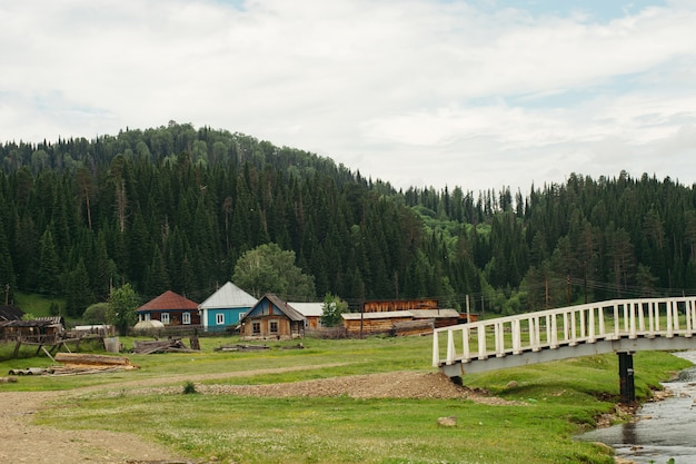Paisagem de casas localizadas perto de montanhas e florestas. ponte sobre o rio. montanha altai. rússia.