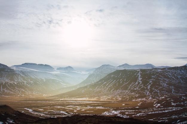 Paisagem de colinas cobertas de grama e neve sob um céu nublado e luz do sol na islândia