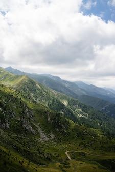 Paisagem de colinas cobertas de vegetação com montanhas rochosas sob um céu nublado