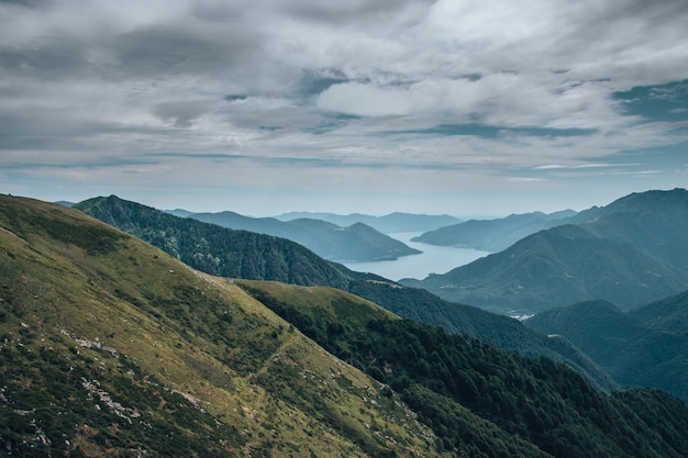 Paisagem de colinas cobertas de vegetação e rodeadas por um rio sob o céu nublado