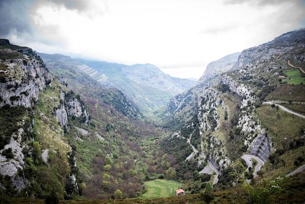 Paisagem de enormes montanhas rochosas cobertas por vegetação verde contra o céu nublado no vale