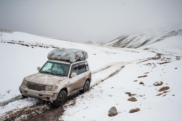 Paisagem de estrada de neve de montanha. carro de jipe 4 x 4 em um passe de montanha