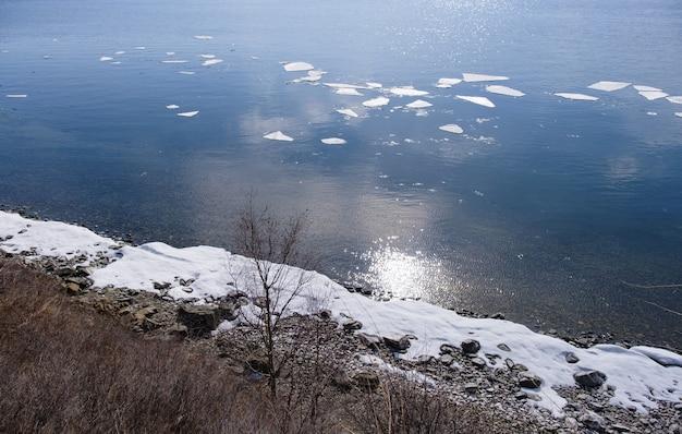 Paisagem de fundo vista do lago baikal com árvores e montanhas em abril em kamen cherskogo, oblast de irkutsk, rússia