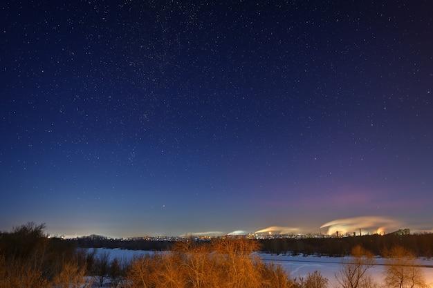 Paisagem de inverno à noite com céu estrelado. zona industrial com bairros residenciais nas margens do rio.