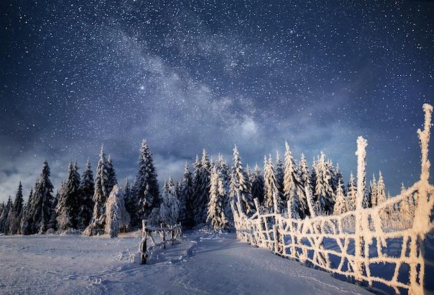 Paisagem de inverno. aldeia de montanha nos cárpatos ucranianos. céu noturno vibrante com estrelas, nebulosa e galáxia. astrofoto do céu profundo.