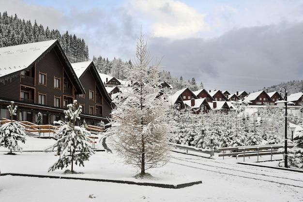 Paisagem de inverno. casas de madeira tradicionais na encosta de uma colina nas montanhas dos cárpatos, rodeadas por pinheiros cobertos de neve.