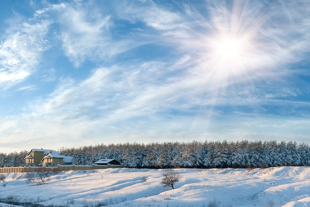 Paisagem de inverno com a casa na beira da floresta, as árvores estão cheias de neve