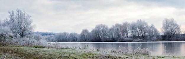 Paisagem de inverno com árvores cobertas de neve na costa do rio, reflexo das árvores no rio, panorama