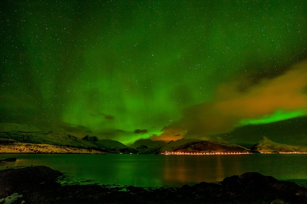 Paisagem de inverno com aurora, mar com reflexo do céu e montanhas nevadas