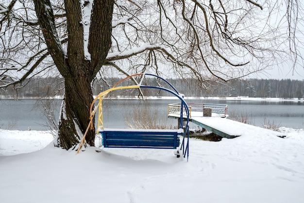 Paisagem de inverno com balanço coberto de neve à beira do lago