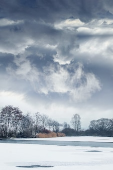 Paisagem de inverno com céu nublado dramático sobre o rio