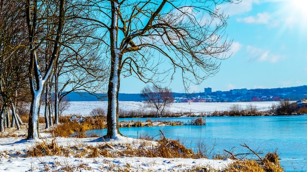 Paisagem de inverno com rio e árvores na costa em tempo ensolarado