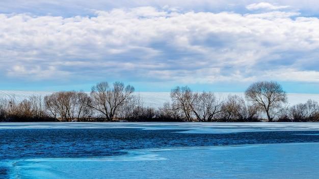 Paisagem de inverno com rio parcialmente coberto de gelo e árvores na costa
