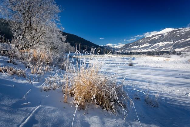 Paisagem de inverno do vale das terras altas coberta pela neve nos alpes em um dia ensolarado