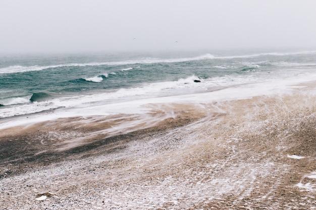 Paisagem de inverno minimalista, vista para o mar durante a queda de neve