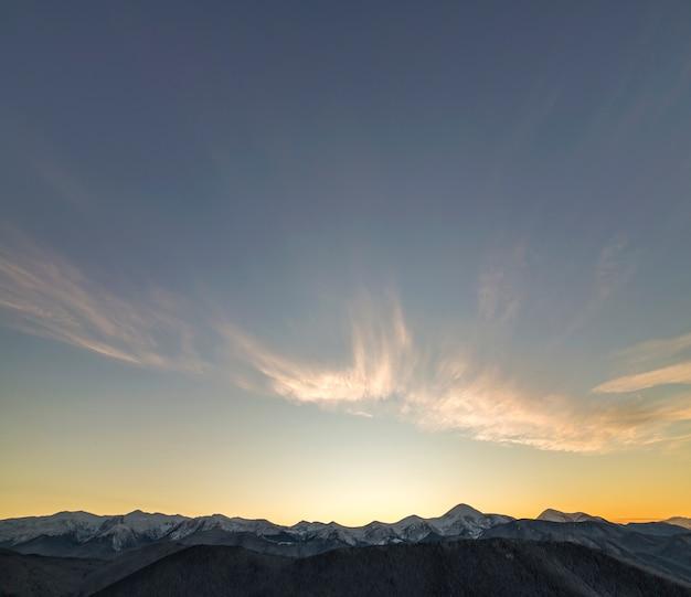 Paisagem de inverno montanha panorama ao amanhecer. picos de montanhas íngremes cobertos de neve e colinas arborizadas com floresta de abetos, levantando o sol brilhante no céu azul claro ao nascer do sol.
